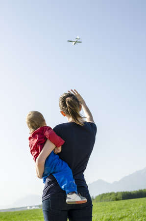 Back view of mum holding her son waving at airplane  photo