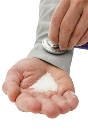overindulgence: Stethoscope on a male hand holding white sugar  Concept of overconsumption of sugar and sugar addiction
