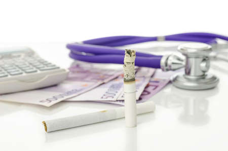 causes: Cigarettes with Euro money, stethoscope and calculator in background  Representing big expenses and great health risk smoking causes  Stock Photo
