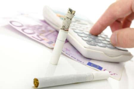 financial burden: Half burned cigarette with calculator and Euro money  Concept of big financial burden smoking is