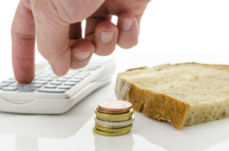 time deficit: Slice of bread with Euro coins and male hand calculating monthly food expenses.