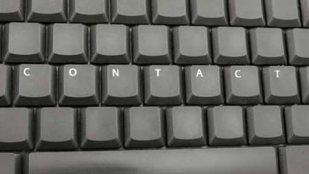 Top view of word contact spelled on computer keyboard. photo