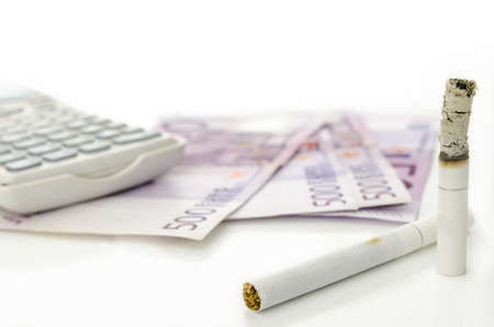 Half burned cigarette with Euro money and calculator in background. Concept of expensive habit. photo