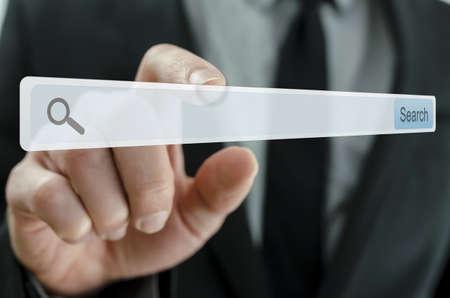 lien: Homme d'affaires pointant barre de recherche sur l'écran virtuel.