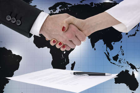 handshake: Male and female  hands shaking over signed contract  Business or political concept