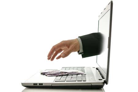 ノート パソコンの画面をものにお金を盗むために手を差し伸べる手。 写真素材