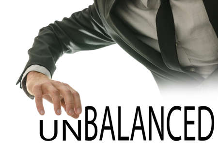 unbalanced: Male hand pushing away letters UN of the word Unbalanced.