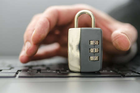 Male hand stealing padlock off computer keyboard. Stock Photo - 20213986
