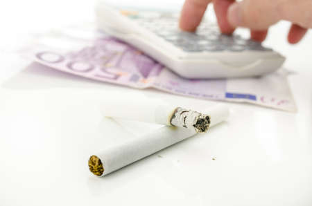 Half burned cigarette with male hand calculating costs of smoking addiction. photo