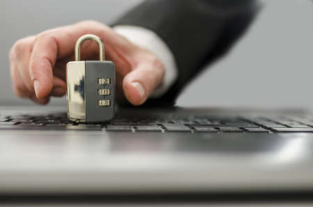 computer crime: Male hand coming out of computer screen and stealing padlock from keypad.  Concept of internet crime. Stock Photo