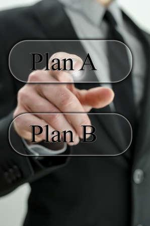 business dilemma: Business man choosing plan A on virtual screen. Stock Photo