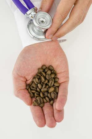 stimulant: Holding stethoscope on coffee addict hand.