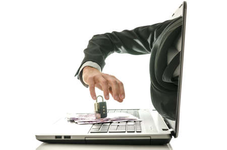 Hacker hand coming out of laptop monitor trying to steal ones money secured with padlock. photo