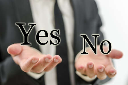 business dilemma: Hand of businessman weighing word Yes and No. Concept of decision making.