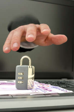 copyrights: Hand coming out of computer monitor stealing padlock from keyboard.  Stock Photo
