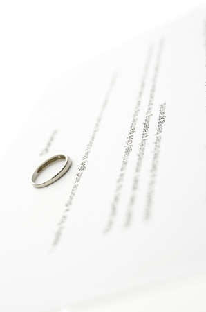 broken contract: Detail of wedding ring on divorce papers. Stock Photo