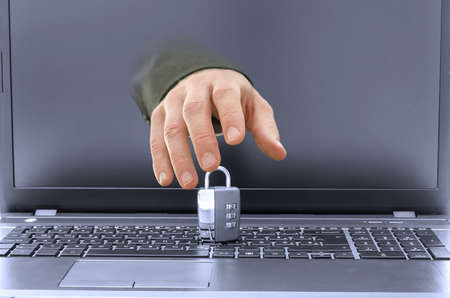 coming out: Closeup of hacker hand coming out of laptop screen trying to steal or break a padlock on keyboard. Stock Photo