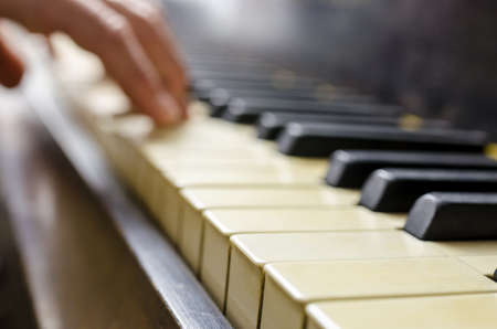 Detail of pianist hand playing vintage piano. photo