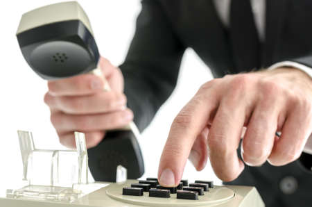 Detail of businessman holding handset of an old telephone and dialing a phone number. Over white background. photo