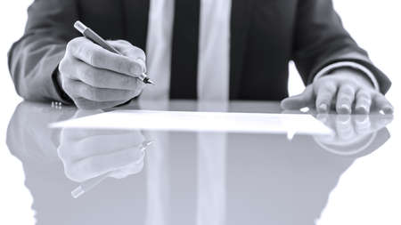 Detail of businessperson or lawyer signing and reading legal papers. Isolated over white background.