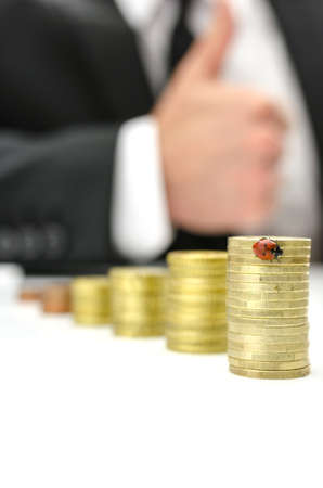 Growing stacks of coins with ladybug on the tallest one. Businessman with thumbs up sign in background. Stock Photo - 21068424