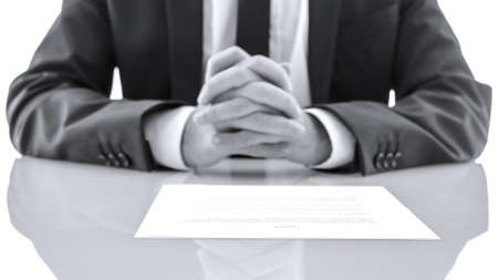 testimony: Detail of lawyer sitting at white desk with his hands together. Giving advice concept. Stock Photo