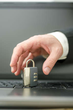 Hand of a hacker trying to steal a padlock from laptop keyboard. Stock Photo - 21071015