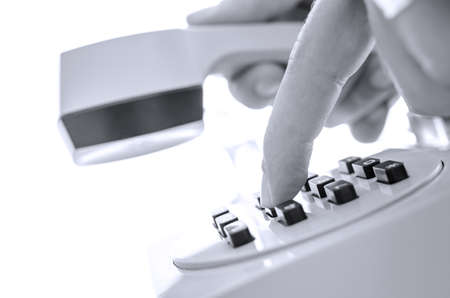the outdated: Side view of dialing a phone number on an outdated telephone with picked up receiver.