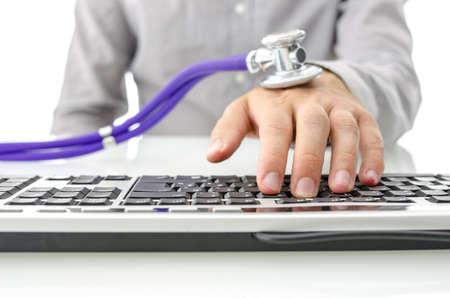 Stethoscoop op mannelijke hand typen op de computer. Concept van het werk of internet verslaving. Stockfoto