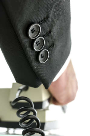 Rear view of businessman hanging up telephone receiver. photo