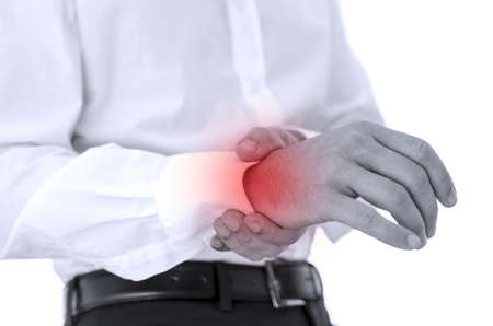 wrist pain: Man holding his injured wrist with red color emphasizing the pain.