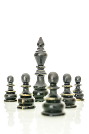 Old black chess figures. King protected by pawns. Isolated over white background. photo