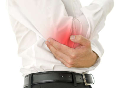 Closeup of man in suit holding his painful injured elbow. Red spot emphasizing sore area. Stock Photo