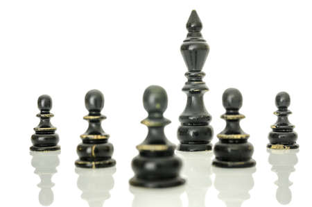 Old chess figures on white desk with reflection. Black king protected by black pawns.  photo