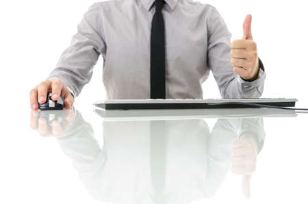 Front view of satisfied businessman siting at his white office desk showing thumbs up sign. Isolated over white background. photo