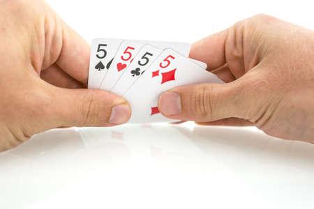 jeu de carte: Quatre cartes à jouer avec le numéro cinq dans les mains du joueur mâle isolé sur fond blanc