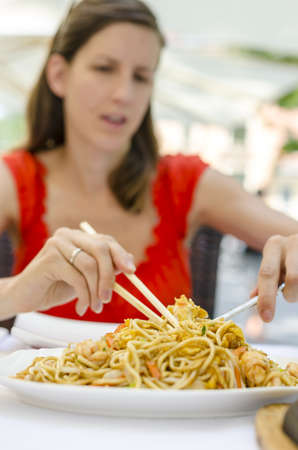 Young woman eating delicious chinese noodles with shrimps and vegetables in restaurant. photo