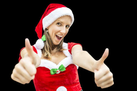 christmasy: Cheerful miss Santa showing thumbs up sign. Isolated over black background.