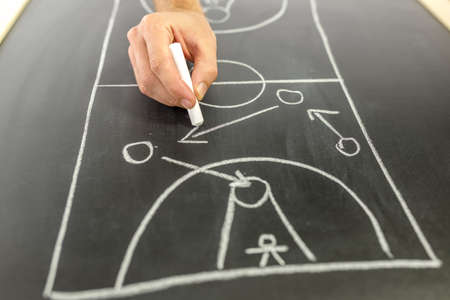 instructions: Closeup of basketball coach drawing game strategy on black board. Stock Photo