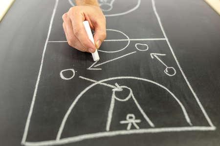 istruzione: Primo piano di allenatore di basket disegno strategia di gioco a bordo nero. Archivio Fotografico