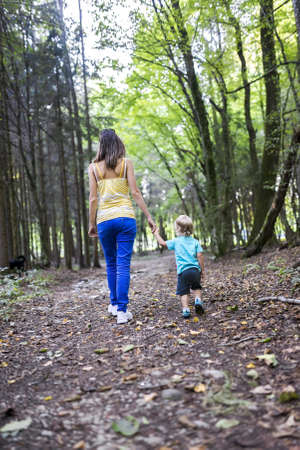 Rear view of young mother and her toddler son spending quality time together walking in the woods. photo