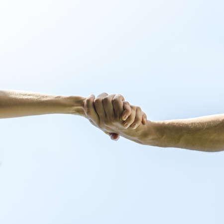 manos unidas: Vista inferior del apretón de manos sobre el cielo azul claro.
