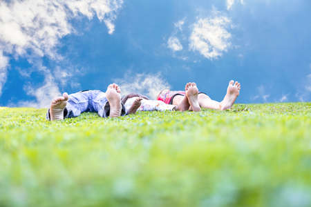 Young couple with their adopted african child lying in green grass. Concept of family happiness. photo