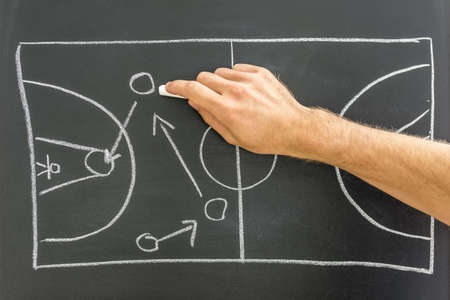 offense: Closeup of coach drawing basketball game strategy on black board. Stock Photo