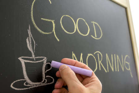 Closeup of cafe owner writing good morning sign on black board  photo