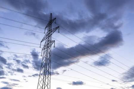 over voltage: High voltage electric tower over cloudy sky at dusk.