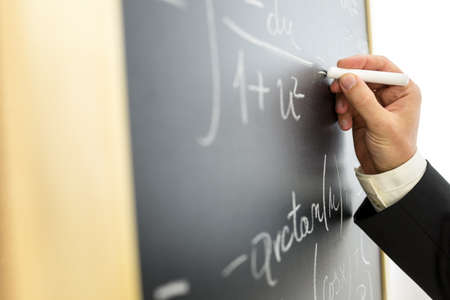 Closeup of college math professor writing complicated equation on black board. photo