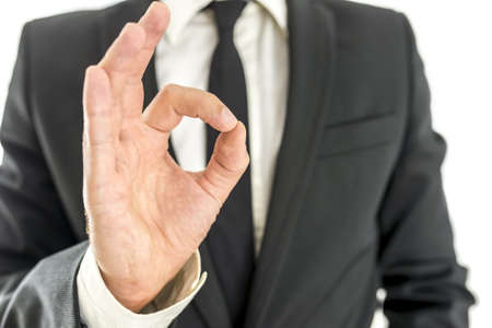 Closeup of satisfied businessman showing an OK gesture. photo