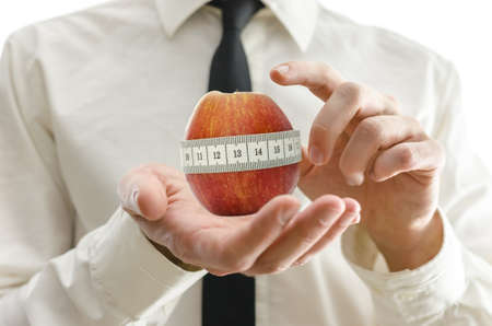 weight loss plan: Closeup of weight loss coach pointing to apple wrapped with measuring tape in interface. Stock Photo