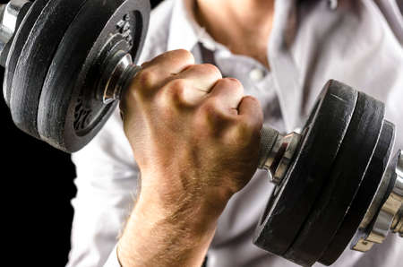potency: Closeup of businessman lifting weights.  Stock Photo
